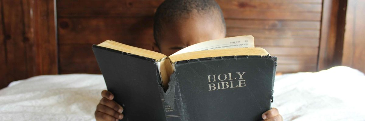 Child reading well-worn Bible