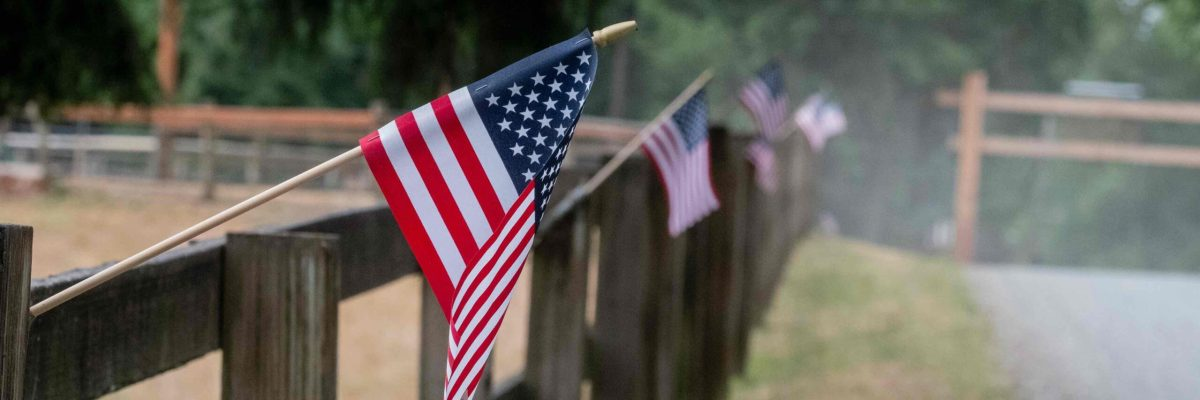 American flags waving from fenceposts