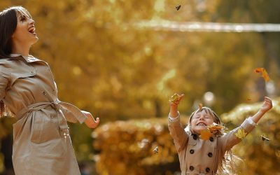 mother and daughter enjoy fall leaves