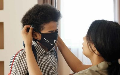Mother puts mask on child