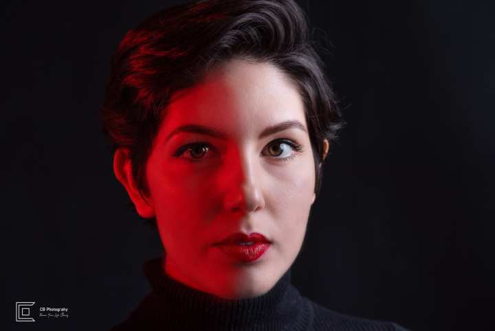 Low key beauty studio headshot with a black background and red color cast by Photographer in Tokyo Cristian Bucur