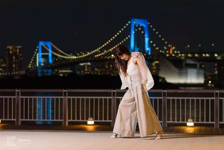 Portrait photography photoshoot at night in Odaiba with Rainbow Bridge lit in the background