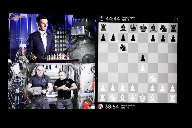 Dos astronautas disputan partida de ajedrez con un campeón en la Tierra