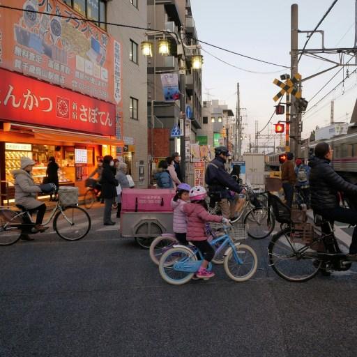 自転車で踏切待ちをしている老若男女の写真