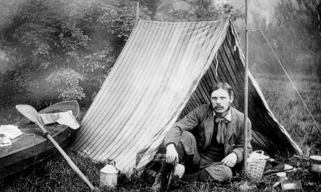 屋外でカヌーと簡素なテント、調理器具などに囲まれて座っているHoldingの写真