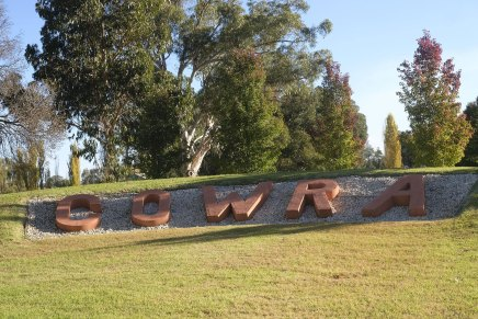 A tree-lined hill features a garden with large timber letters spelling C O W R A
