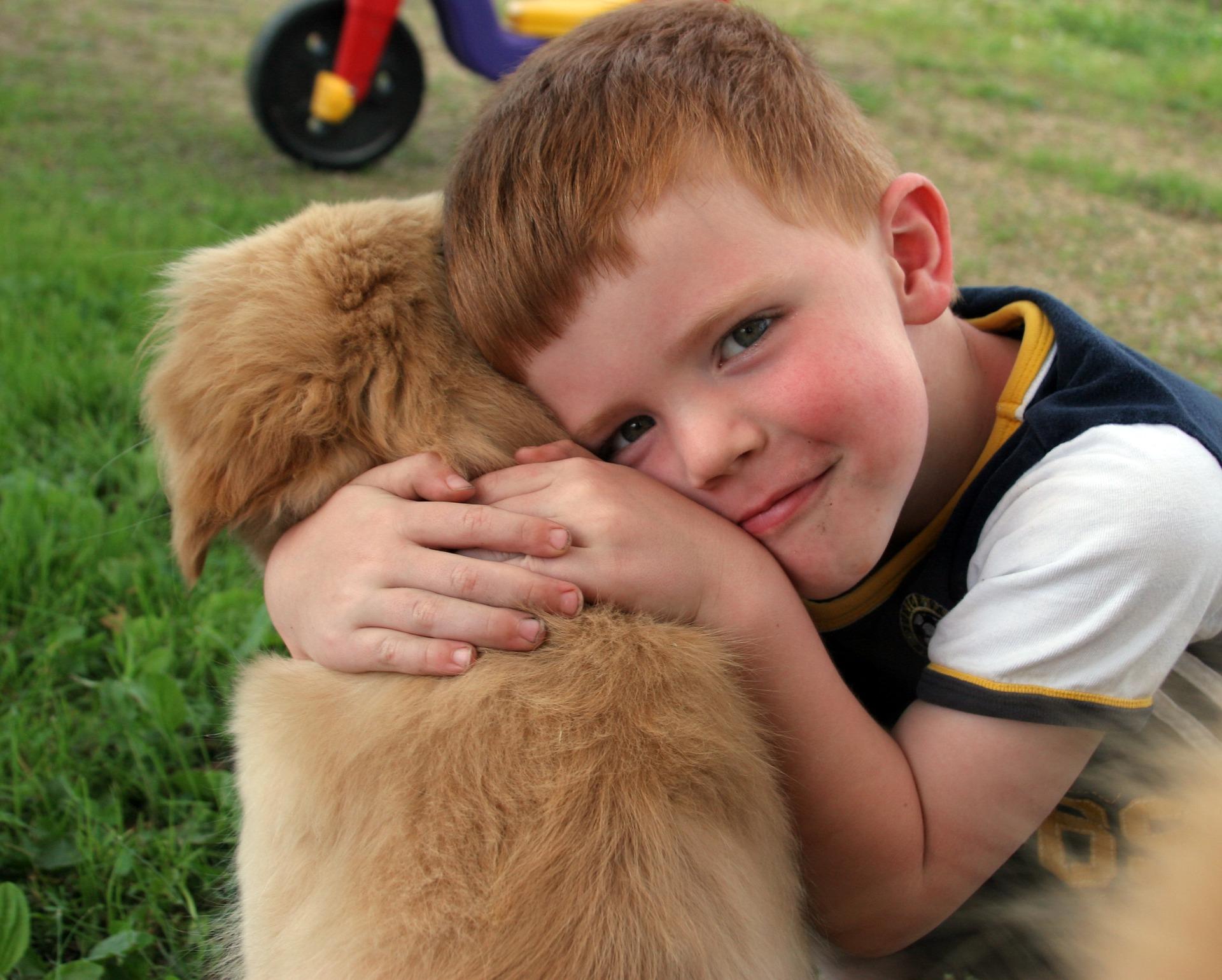 boy cuddling puppy dog in garden