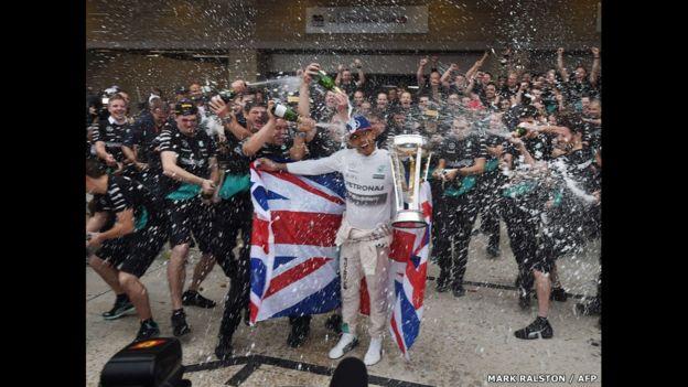 Una lluvia de champagne baña al piloto británico Lewis Hamilton y a los miembros de la escudería Mercedes tras ganar su tercer título mundial en el Circuito de las Américas en Austin, Estados Unidos.