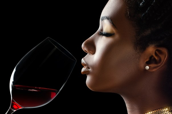 Macro close up low key portrait of sensual woman smelling red wine.Side view of girl with red wine glass next to face against black background.