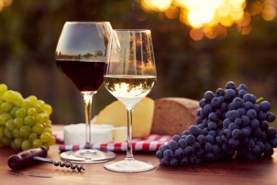 Two glasses of white and red wine with food at sunset, toned.