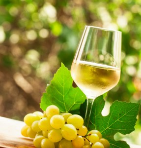 Coid white wine and green grapes on natural blurred background with bokeh, selective focus.