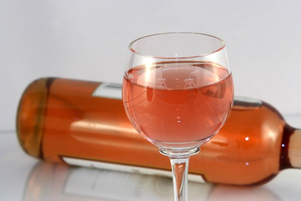 A refreshing glass of white zinfandel with the bottle in the background.
