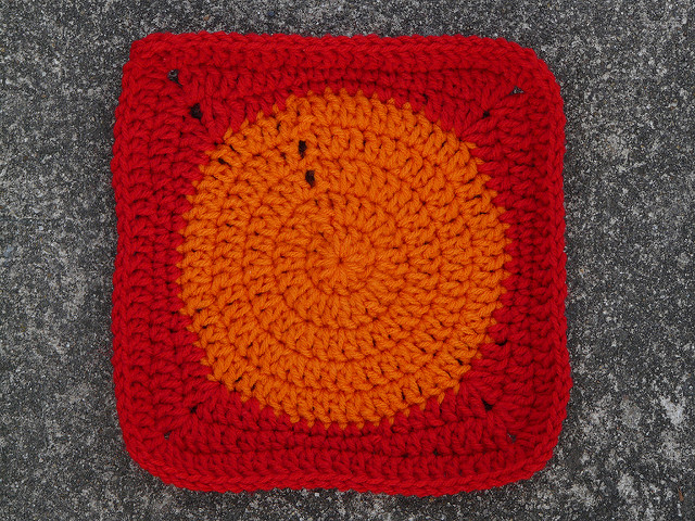 A red crochet square with an orange crochet center