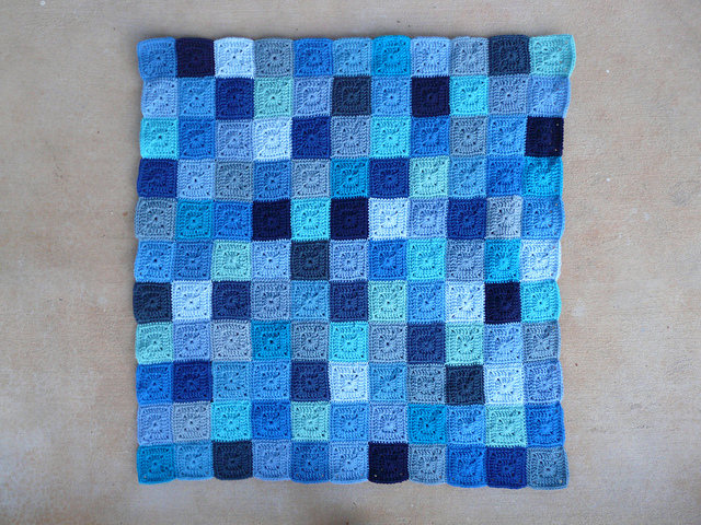 Eleven of thirteen rows of a crochet blanket made of blue crochet squares