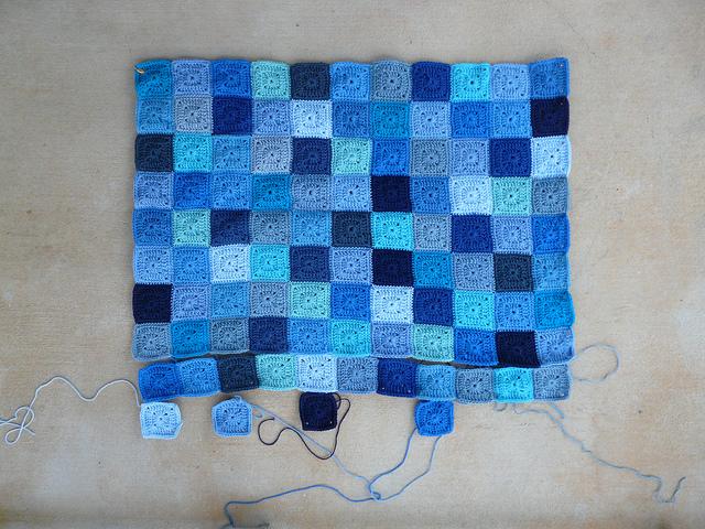 a crochet blanket made of blue crochet squares