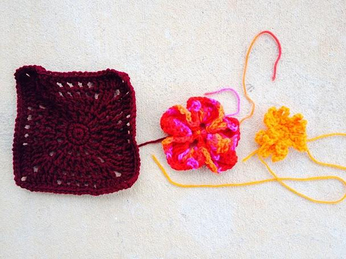 Crochet granny square with crochet flower pieces to appliqué