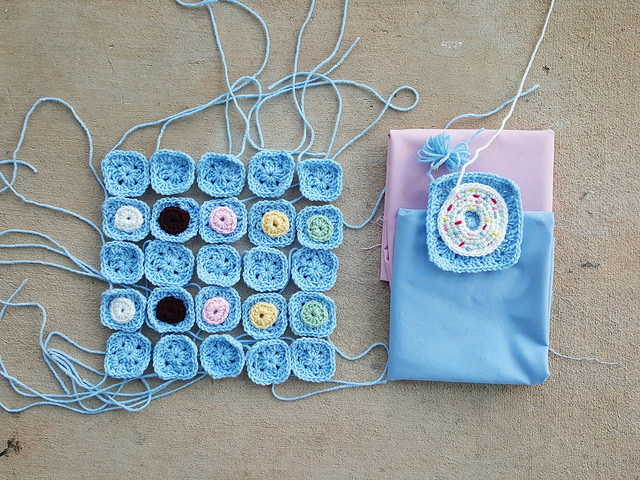the pieces of a future crochet donut bag with the fabric for lining