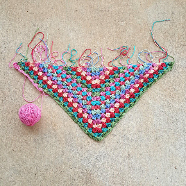 Crochet poncho for a child made with pink, blue, green and orange yarn