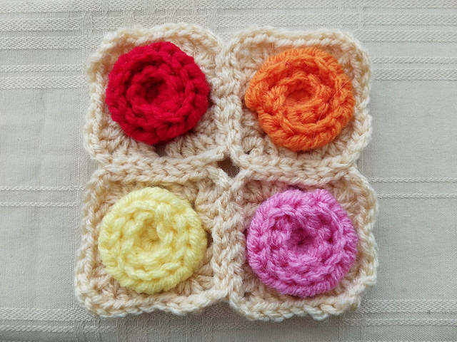 A four patch of crochet rose centered granny squares