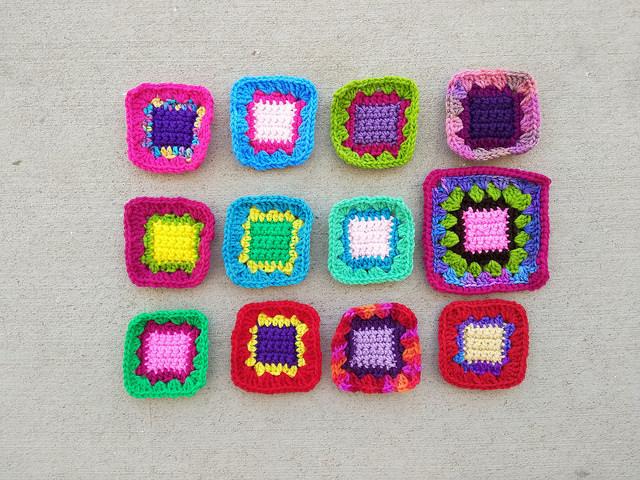 Twelve crochet remnants waiting to become five-inch crochet squares