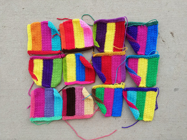 Twelve rehabbed crochet squares ready to have the ends woven in