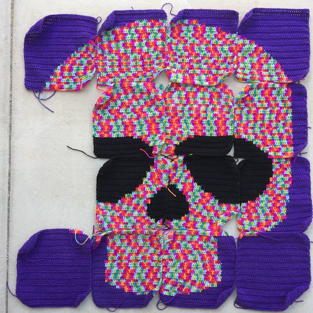 A nearly completed Day of the Dead crochet yarn bomb made with variegated yarn for the skull