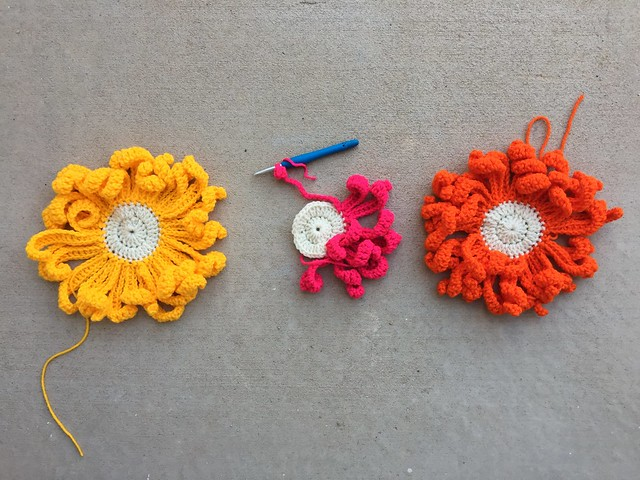 Three large crochet flowers all in a row