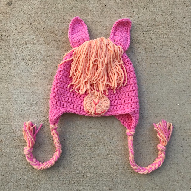 A crochet llama hat made from pink and light orange yarn during a very busy crochet hat season