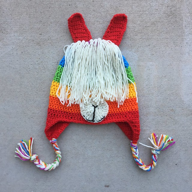 A crochet llama hat for an adult made with six colors of the rainbow