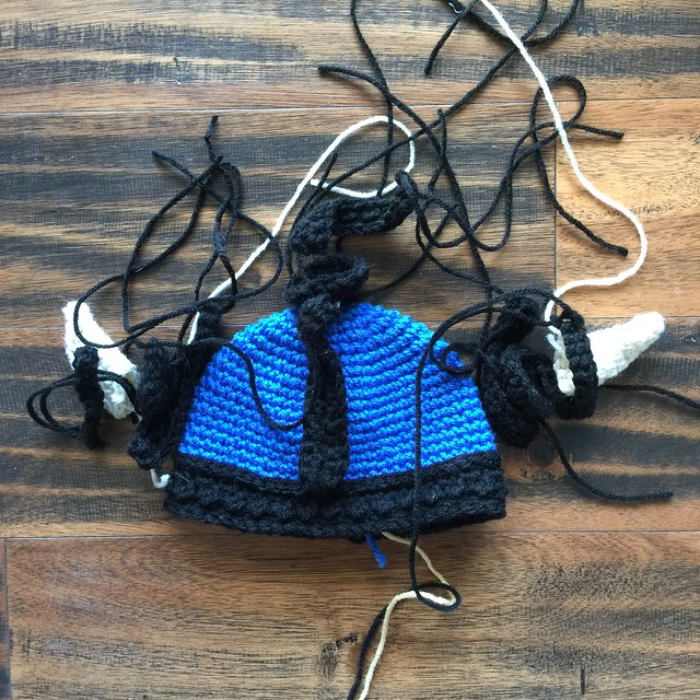 All of the pieces for a blue and black crochet Viking helmet