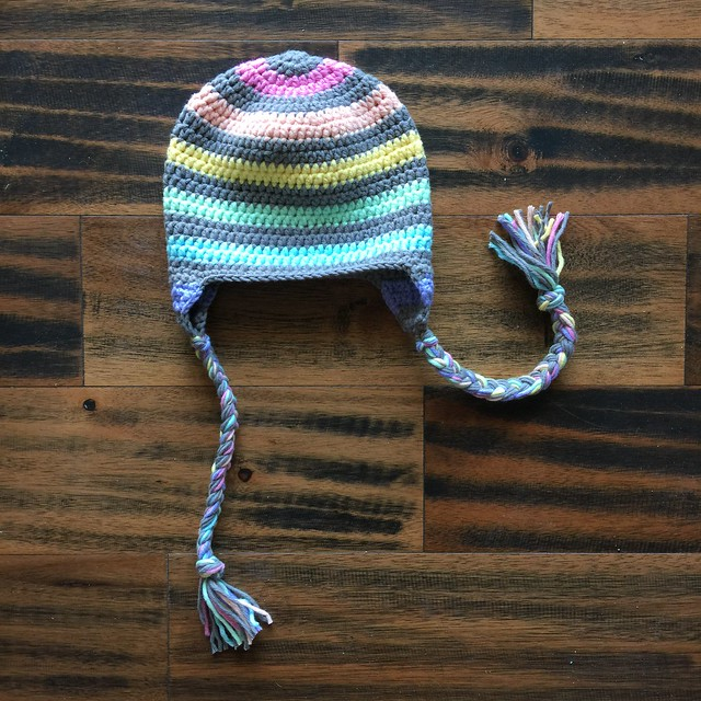 A striped crochet hat for a toddler with earflaps and braids.
