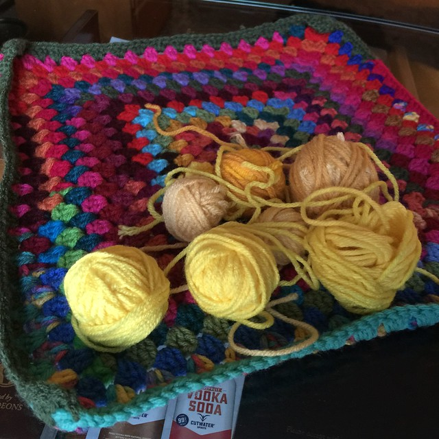 A collection of yellow yarn scraps on top of a multicolor granny square