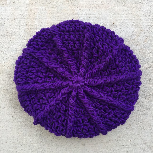 A top down view of the completed purple textured crochet newsboy hat