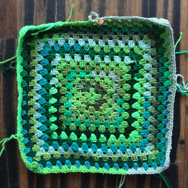 The crochet square made of scraps of green yarn after more rounds are added