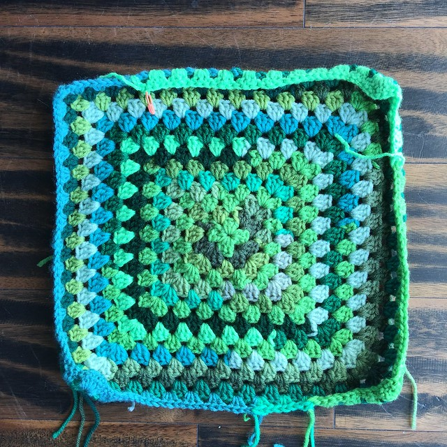 A crochet square made of scraps of green yarn