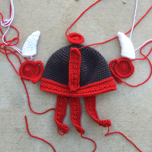 A gray and red crochet Viking helmet for a baby
