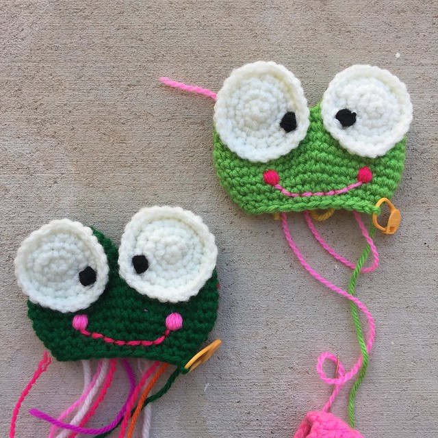 Two amigurumi frogs get their embroidered cheeks and smiles