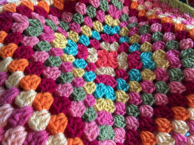 The center of a multicolor great granny square blanket.