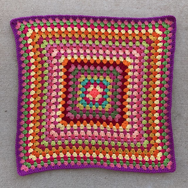 The first twenty-four rounds of a multicolor granny square blanket. The last rounds demonstrate how one color can