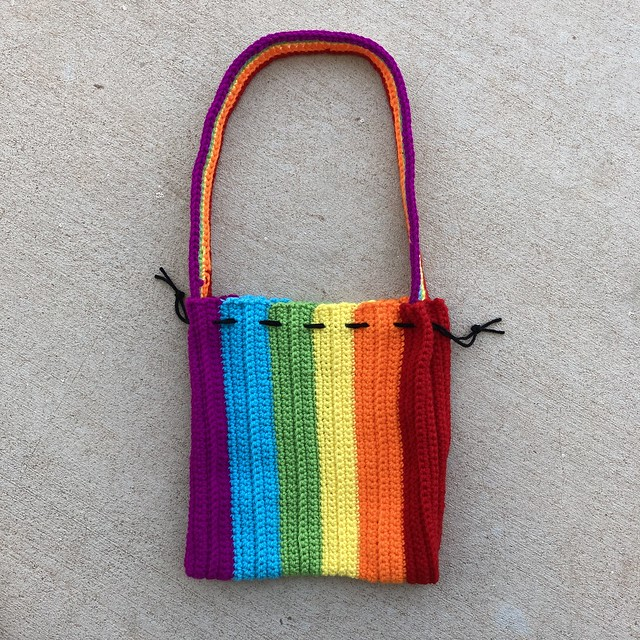 A rainbow drawstring crochet purse ready to be pulled closed