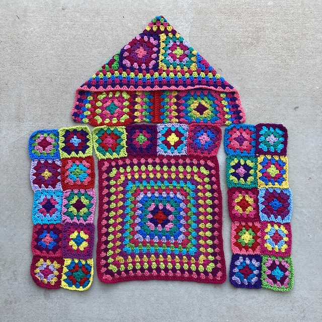Four pieces of a granny square cardigan blocked and ready to be joined