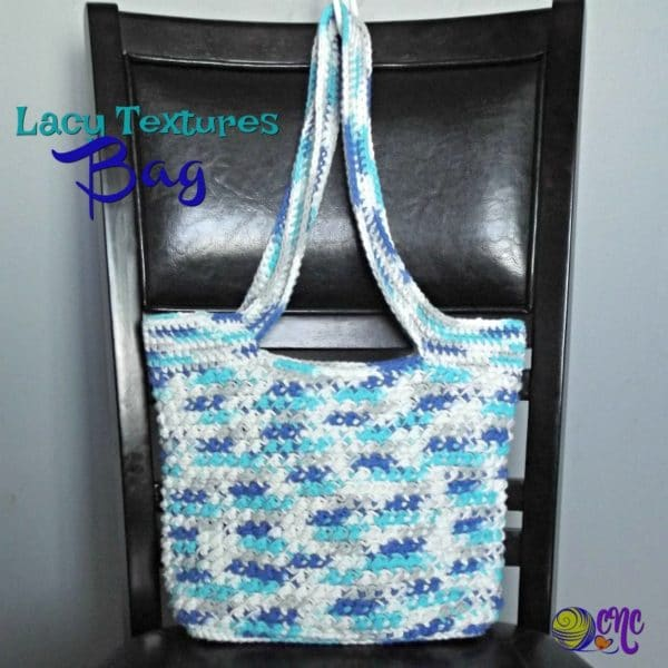 A textured crochet bag worked up in a variegated cotton yarn sits on a chair.