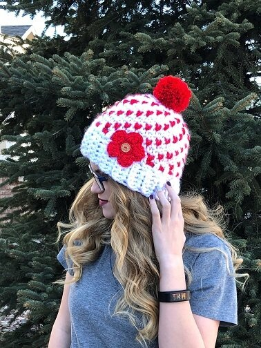 Valentine's day is coming and this hat full of hearts is the perfect accessory for the day of love and everyday! The Heartful Winter Hat is a women's hat that is meant to fit loosely. Worked by carrying the coordinating color behind the stitches, the double layer creates a warm hat for even the coldest of days. A quick and easy pattern, the fair isle style hat is worked in super bulky yarn and can be completed in just over an hour for a quick turnaround. Your customers and loved ones are going to want one in every color! The women's beanie pattern with hearts throughout is a written pattern with photo tutorials for the color changing stitches and the pompom. While the pattern indicates that it is for intermediate crocheters, once the color change is figured out, the hat is a breeze to make! nopin =