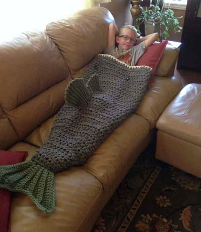 Photo of a boy with eyeglasses lying on a leather sofa using the Large Mouth Bass Blanket