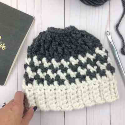 This is such a fun crochet pattern: houndstooth messy bun hat! It works up so quickly and looks harder than it is! I can't wait to make one in every color for my craft fairs this season. #messybunhat #crochetpattern #ponytailhat #bunbeanie #kaydencebunhat #madewithatwist #easycrochetpattern