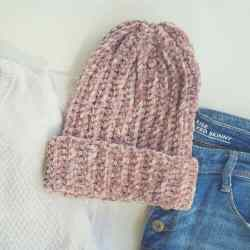 Photo of the crocheted Penelope Velvet Beanie with a white shirt and blue jeans