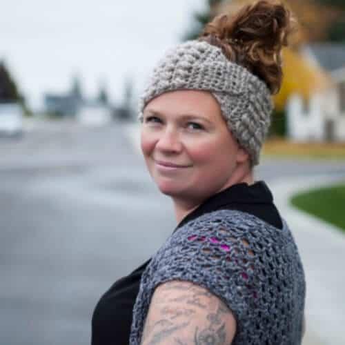 Photo of a woman wearing the crocheted twisted headband ear warmer