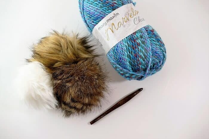 Photo of Giveaway products, Marvelous Chunky Yarn in Berry Blue colorway, three faux fur pompoms, and a size L Crochet hook.