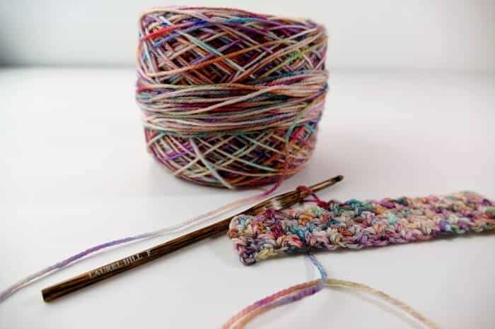 Photo of a ball of multicolored yarn, a small crocheted swatch, and a size F Laurel Hill Wooden Crochet Hook
