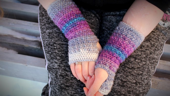 Women wearing a pair of crochet fingerless gloves with her hands in her lap. The gloves gradient from a white to gray, to purple, to blue.